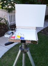 "Binder clips hold on the canvas panel and tea canister and Altoid tin ""side-cars."""