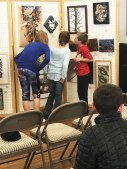 The students are invited to look at the works and think of questions they might want to ask.